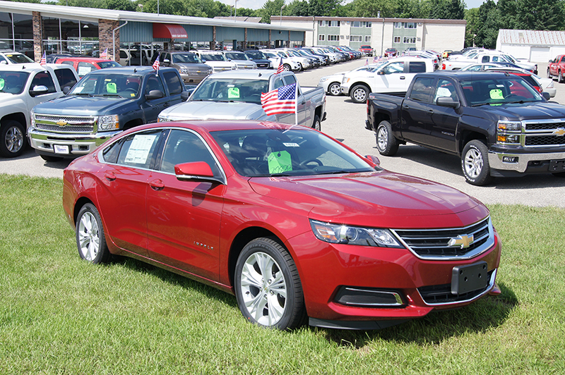 A Chevrolet impala car parked on a grassy patch of land. Various other cars of different make and model are parked behind in what seems like a parking lot.