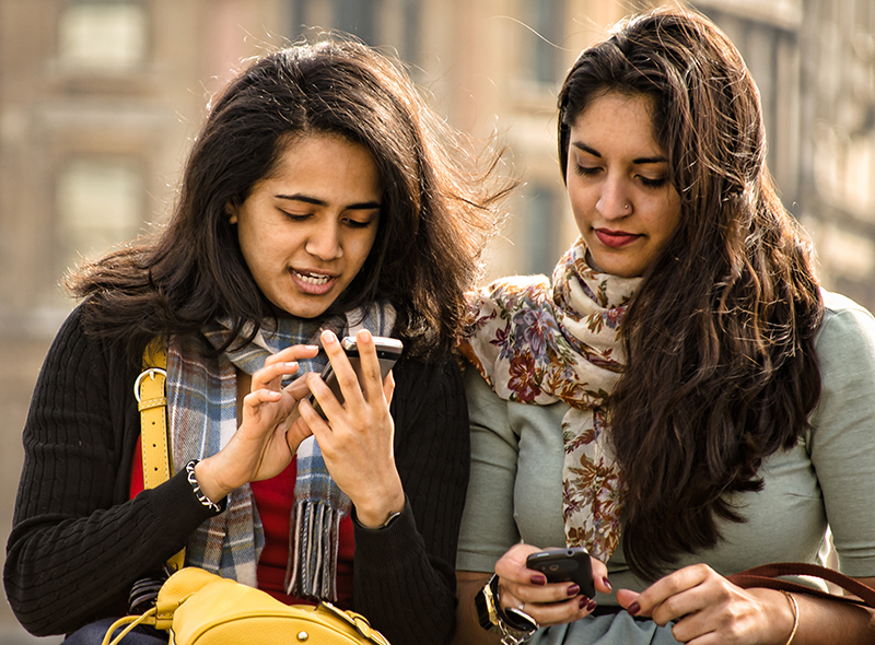A photo shows two young women using mobile phones.