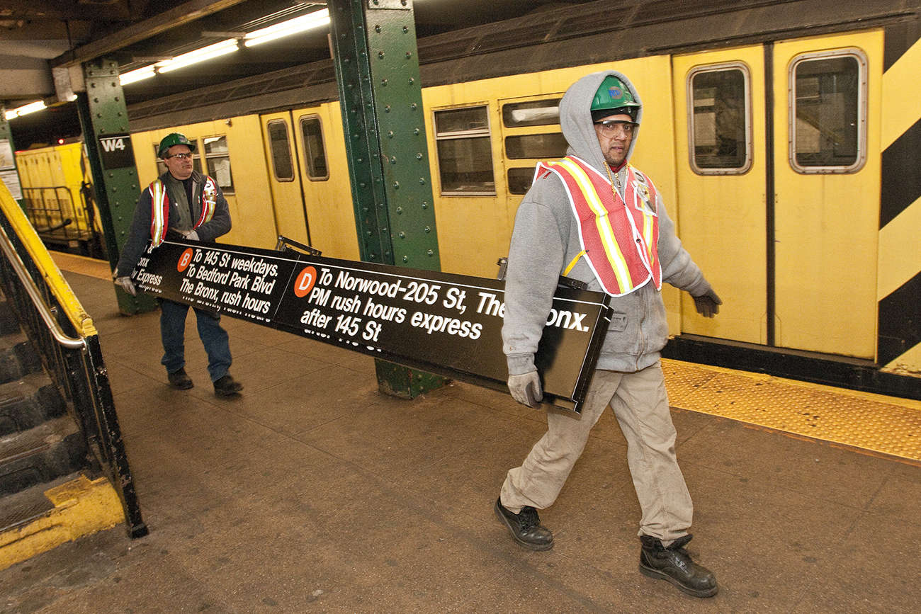 A photo shows two metro workers at work. They carry a destination sign inside a subway station.