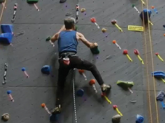 A picture shows a person in a harness ascending a climbing wall.