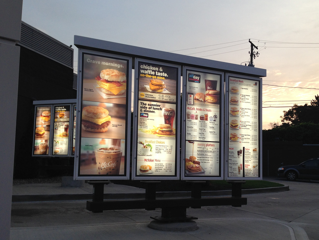 A photo shows a McDonald's drive-through menu put outside the restaurant. The pages of the menu are shown placed in a large lit-up glass display case.