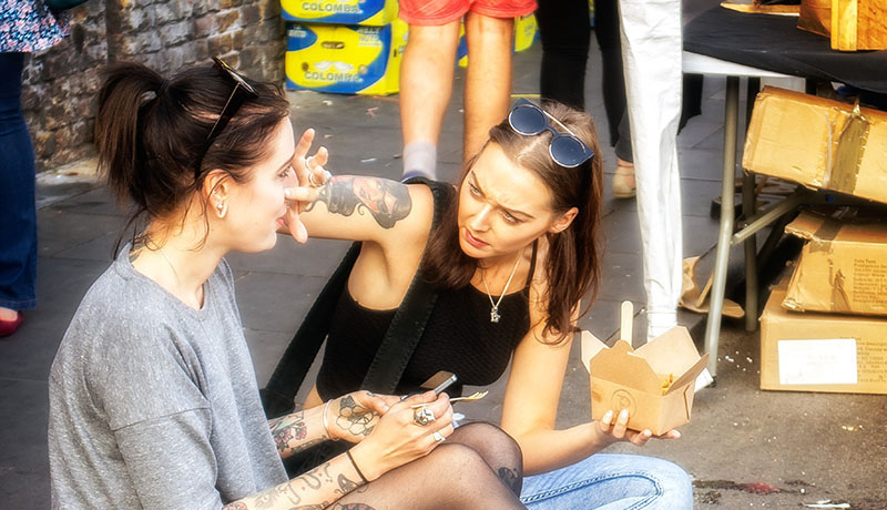 A photo shows two young women sitting on the edge of a busy sidewalk eating a meal. One reaches to the other's face as if to remove a piece of food.