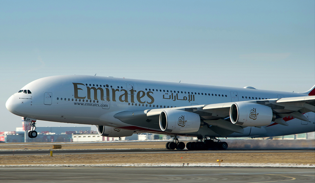 A photograph shows a large, double decker airplane, with the word, Emirates, painted on the side. There is also Sanskrit painted on the side of the plane.