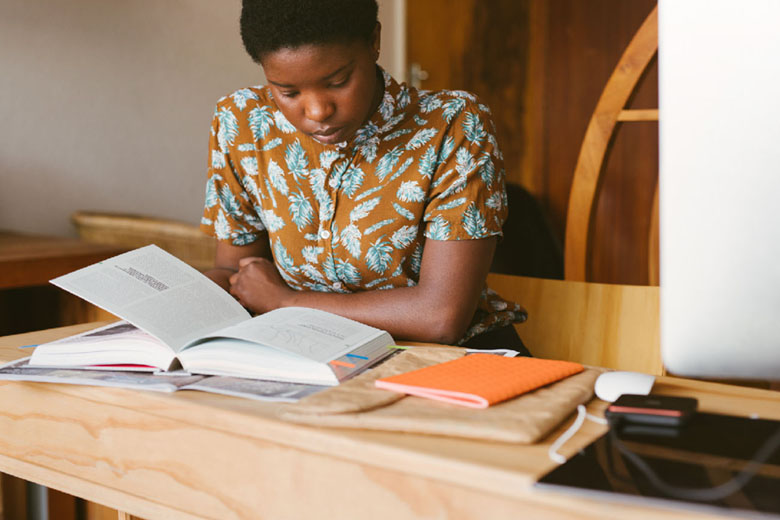 A student sitting at a desk and studying from a textbook.