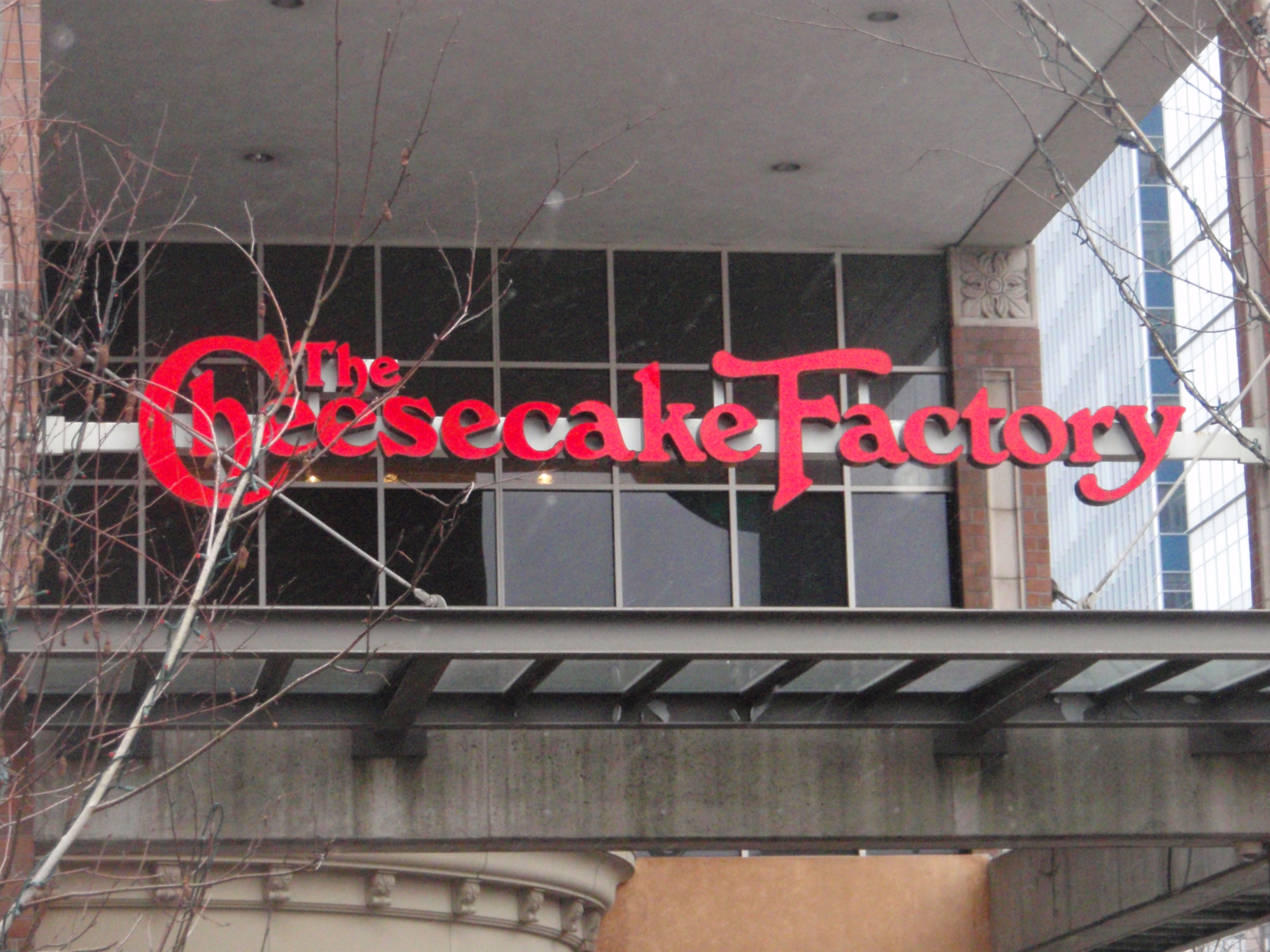 A photograph shows a large Cheesecake Factory sign hanging above the entryway of a building.