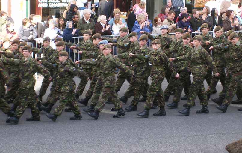 A group of soldiers is shown marching down the road while spectators look on.