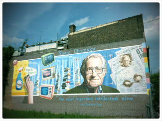 """A photograph shows a mural on the side of a building. The mural includes Chomsky's face, along with some newspapers, televisions, and cleaning products. At the top of the mural, it reads """"Noam Chomsky."""" At the bottom of the mural, it reads """"the most important intellectual alive."""""""