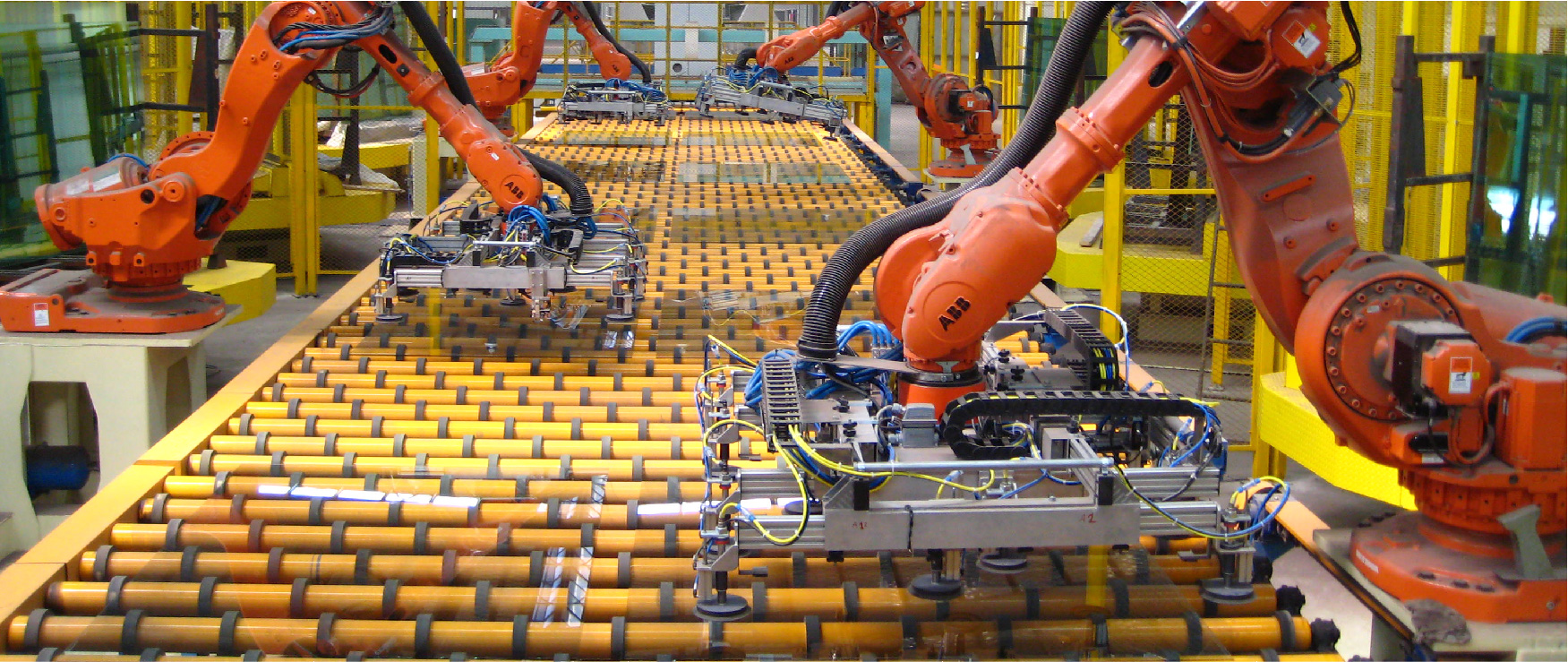 Robot arms loading an unloading sheets of float glass from a rolling conveyor belt.
