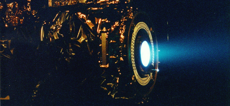 The photo shows a xenon ion engine and a blue glow emitted from it.
