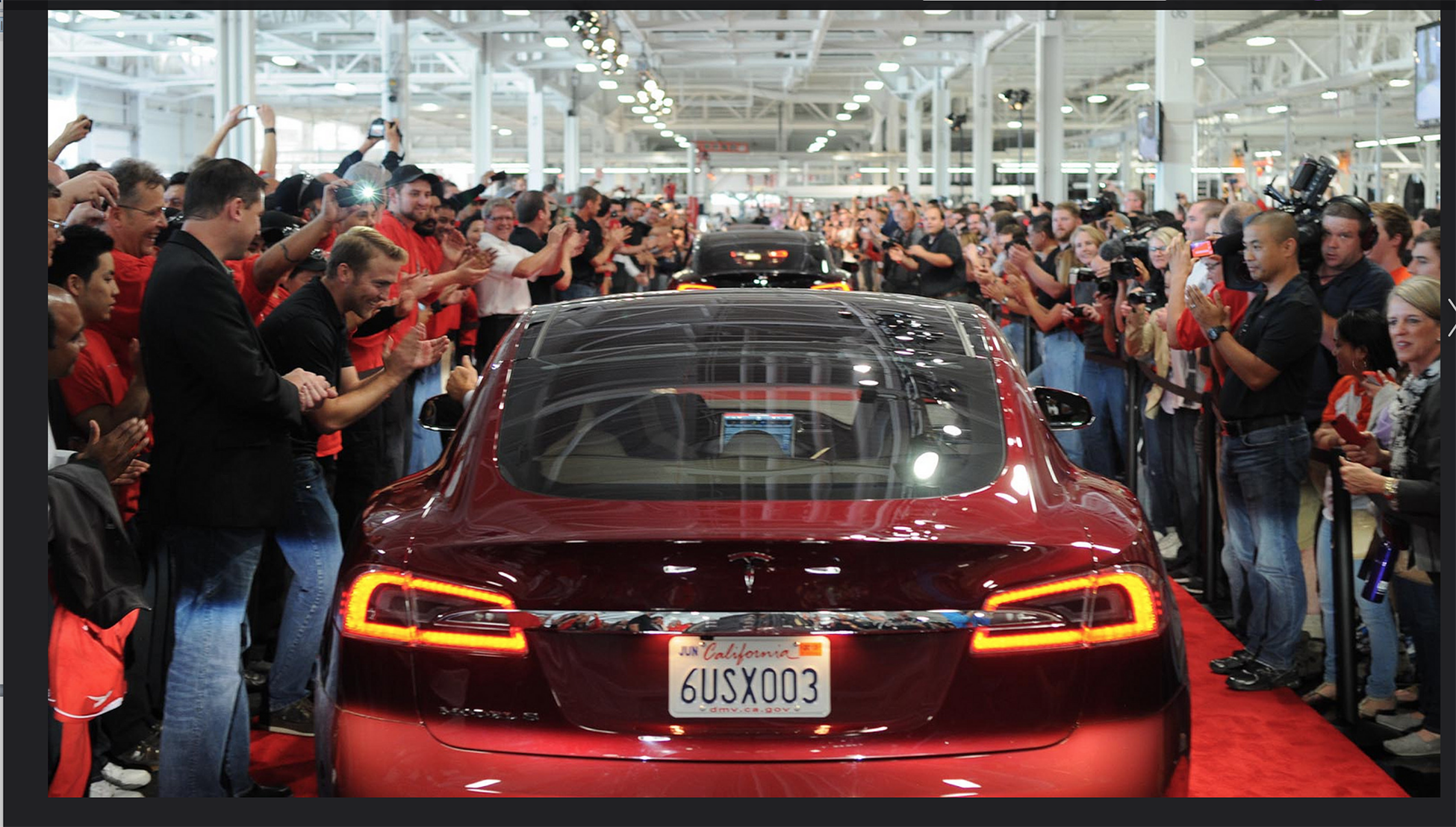 A photograph shows a large crowd cheering on a line of Tesla cars driving down a red carpet path.