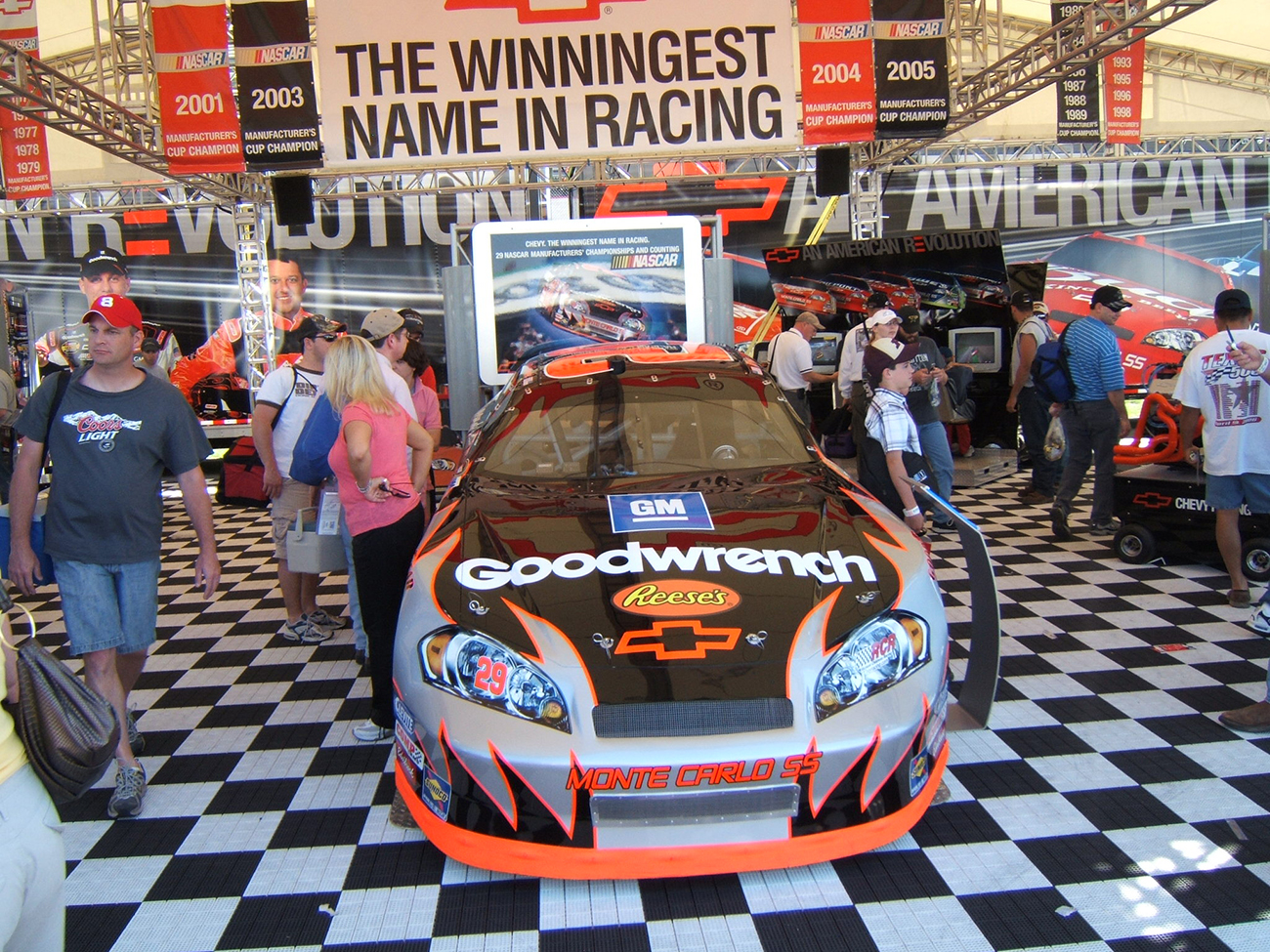 A photograph shows a group of people walking around a Nascar display area. There is a large Chevy racecar parked inside, covered in decals such as G M, Reese's candy, and Good wrench.
