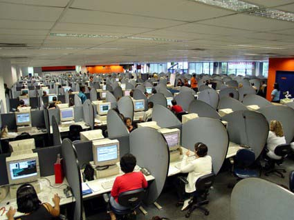 Many people at workstations in a call center are shown here.