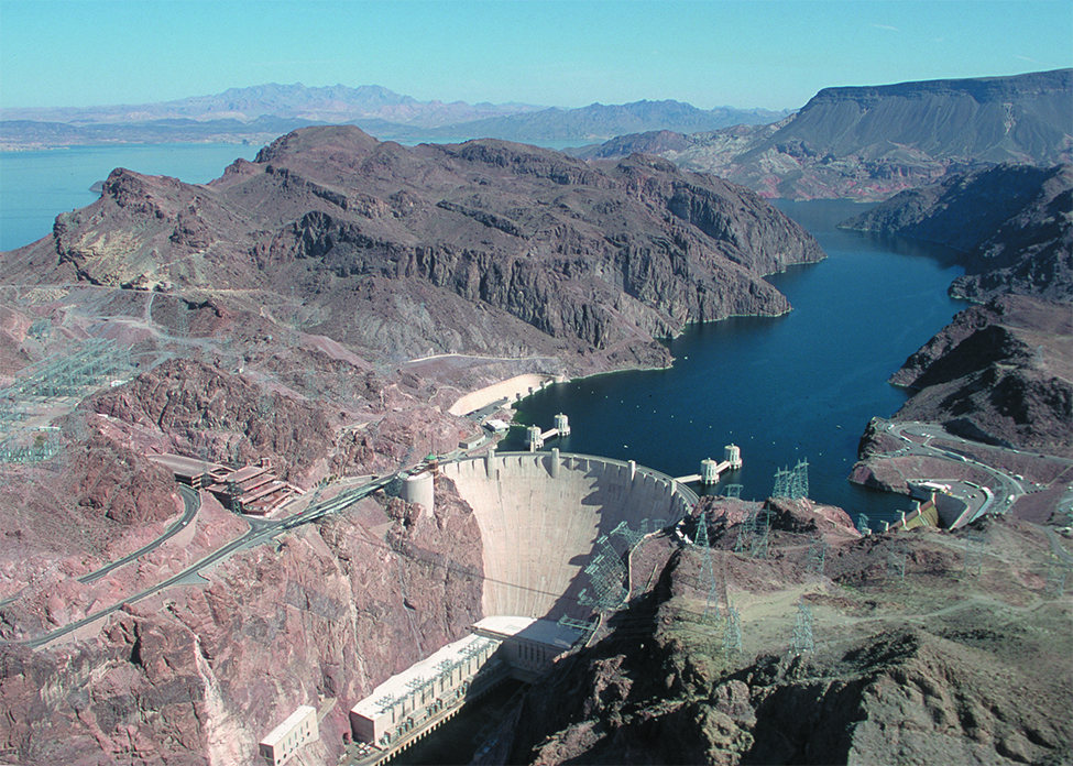 This is a picture of the Hoover Dam. The picture has the dam in the background and flowing water in the foreground below the dam.