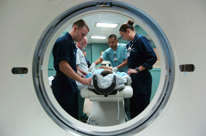 A photographic image taken through the port of a C T scanner, showing a patient on a stretcher surrounded by three nursing staff and a doctor who are taking the patient's C T scan.