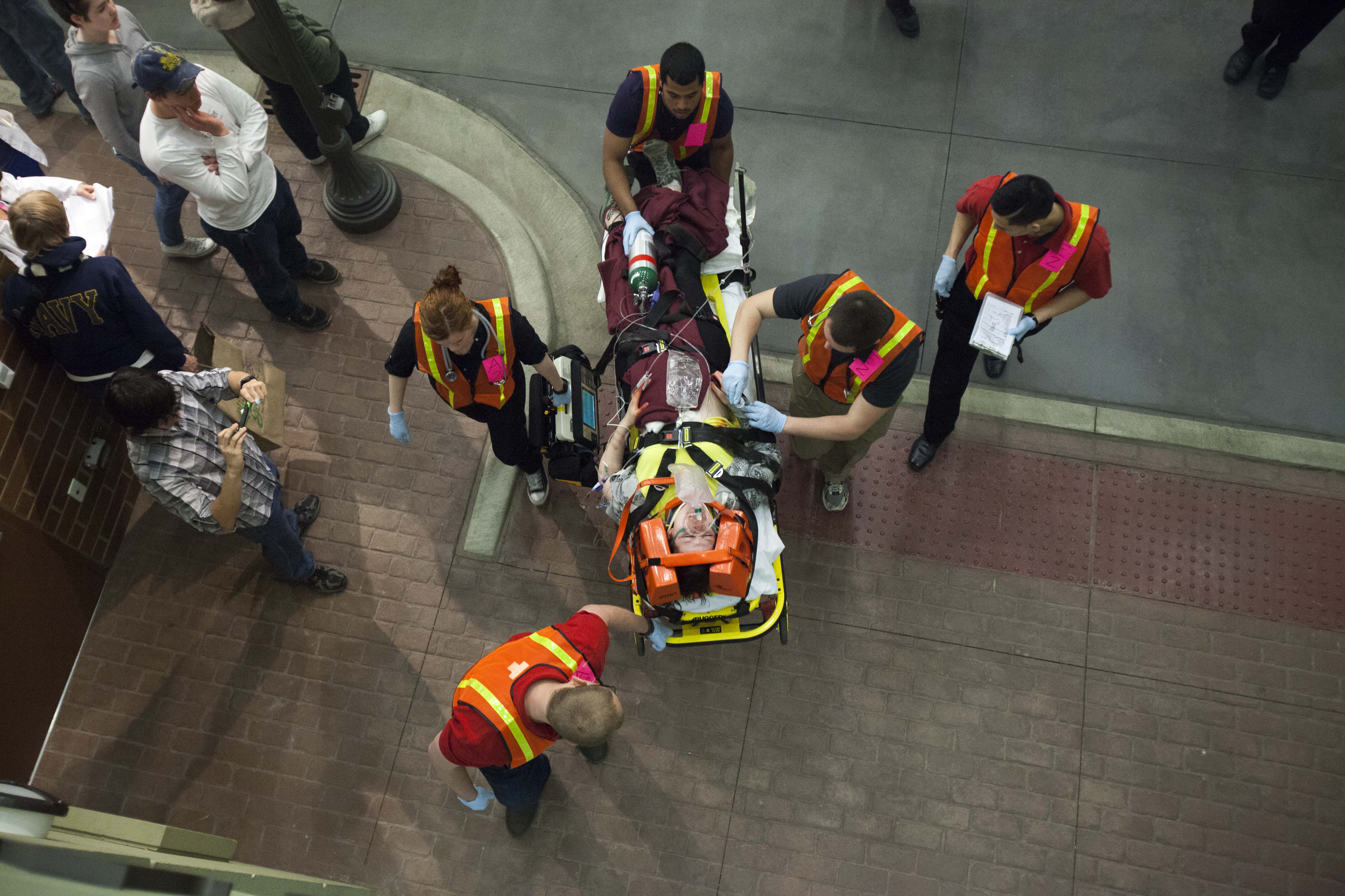 A photo shows the overhead view of a paramedics team of five moving a patient secured on a stretcher through a public place. People stand beside watching them walk away.