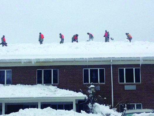 An image of several people standing on top of the roof of a brick building. The roof is covered in snow.