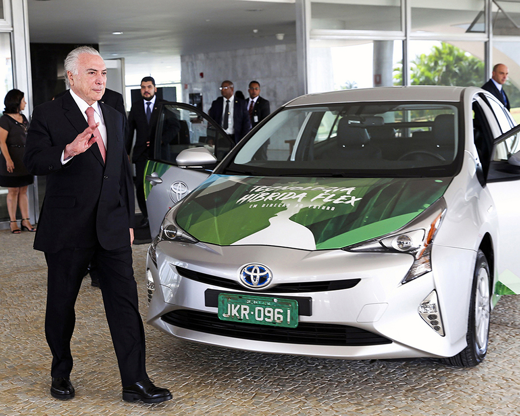 A photo shows Michel Temer waving to the camera as he stands next to a Toyota Prius hybrid electric vehicle at the launch ceremony of the world's first flex hybrid vehicle.