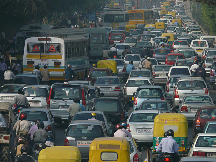 Photograph shows a roadway crowded with cars and motorcycles in Delhi.