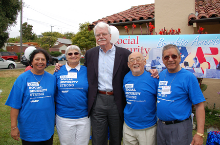 "A tall man with white hair and moustache and glasses in casual business attire is shown flanked by two elderly women on his right and two elderly men on his left. The elderly people are all wearing blue T-shirts reading ""Keep Social Security Strong: A A R P."" A banner in the background can also be seen, reading ""Social Security Benefits America."""