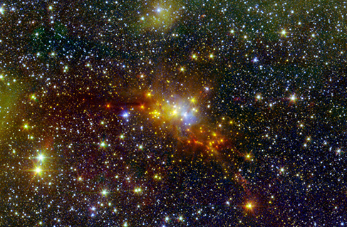 A telescope image showing numerous stars. A bright cluster in the center has yellow, orange and blue stars.