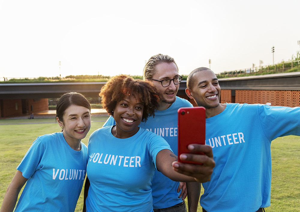 A diverse group of employees wearing volunteer shirts take a photo of themselves with a phone's camera.