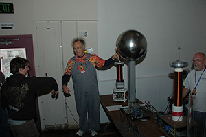 This is a photograph of a man touching the large sphere of a Van de Graaff generator, causing his hair to stand on end. The picture also shows two observers, one of whom has extended his right arm toward the man touching the generator.