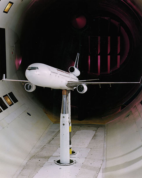 A photograph of a model plane in a wind tunnel.
