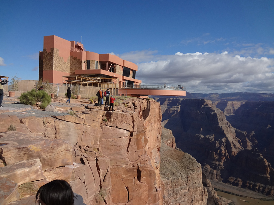 This figure is a picture of the Grand Canyon skywalk. It is a building at the edge of the canyon with a walkway extending out over the canyon