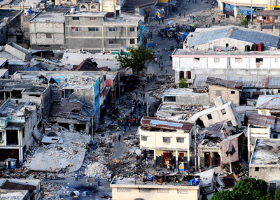 The destruction caused by an earthquake in Port-au-Prince, Haiti. Some buildings are shown on two sides of a street. Two buildings are completely destroyed. Rescue people are seen around.