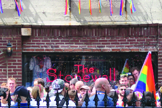"An image of a group of people standing in front of a brick building. A sign in the window of the building reads ""The Stonewall"". A multicolored flag is held by a person to the right."