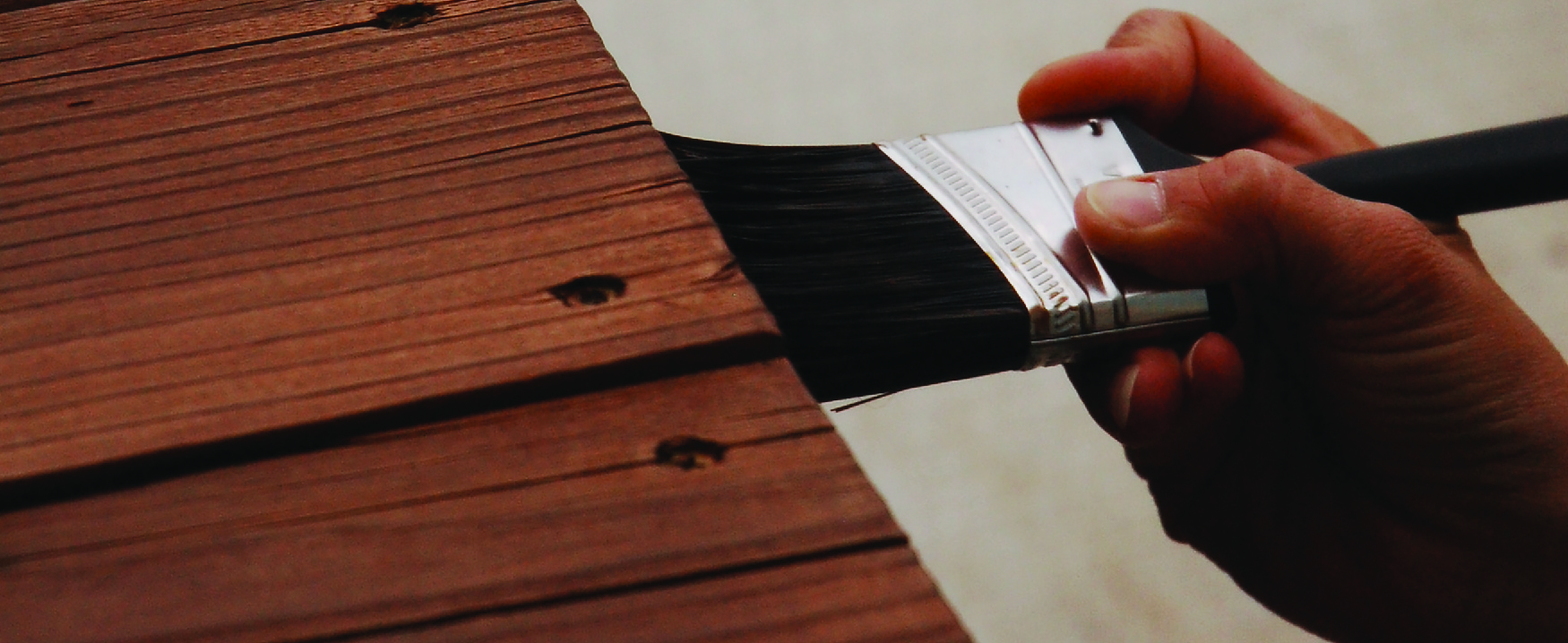 A photograph shows someone holding a brush applying stain to a piece of wood furniture.