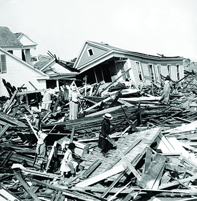 A photograph shows the devastation of the 1900 hurricane in Galveston, Texas. Residents climb among the massive woodpiles from fallen homes. Several other crushed houses are visible in the background.