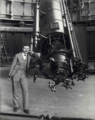 Photograph of Edward Emerson Barnard leaning against a large telescope.