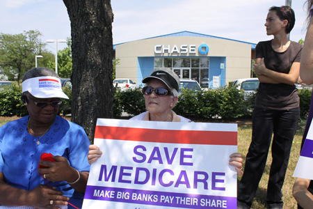 "Two elderly women, one holding a red white and blue sign reading ""Save Medicare: Make Big Banks Pay Their Share,"" are shown sitting under some trees and in front of a suburban bank building. A younger woman, dressed all in black, is shown behind and to the left of the other women."