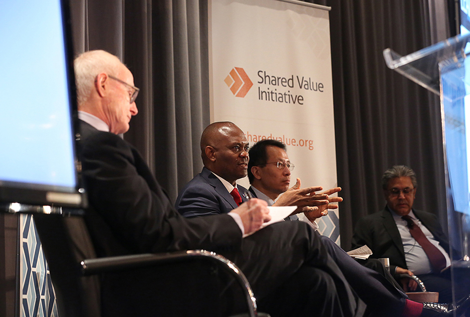 A photo shows Michael E.Porter taking notes during a conversation with Jin-Yong Cai, Tony O. Elurrelu, and Arif Naqvi at the Shared Value Leadership Summit.