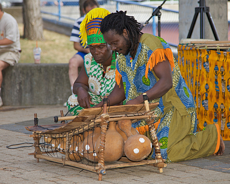 Photograph of two musicians playing on a marimba.