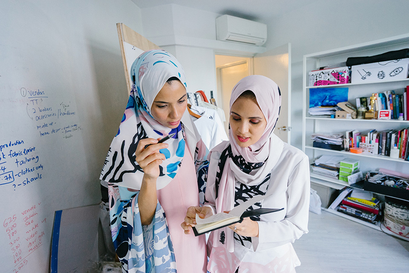 A photo shows two young women in hijabs, looking at a diary while having a serious discussion at their workplace.