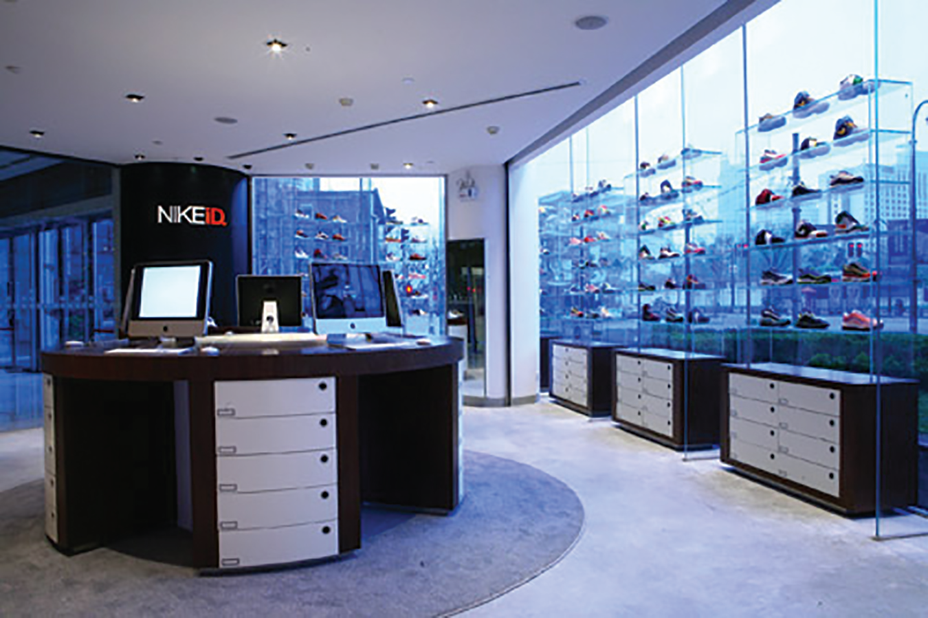 A picture of the inside of a NIKEiD store showing shoes on shelves by glass windows with a view of many tall buildings.