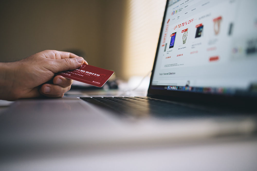 A photo shows a person making a purchase online with a credit card.