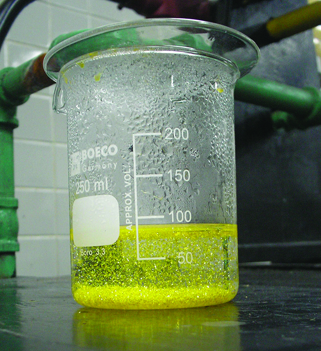 A photograph is shown of a yellow green opaque substance swirled through a clear, colorless liquid in a test tube.