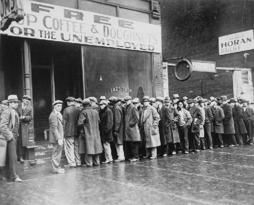 "Photo shows a line of people in long coats and hats standing in line outside a building with a sign that states ""Free Cup Coffee & Doughnuts for the Unemployed""."