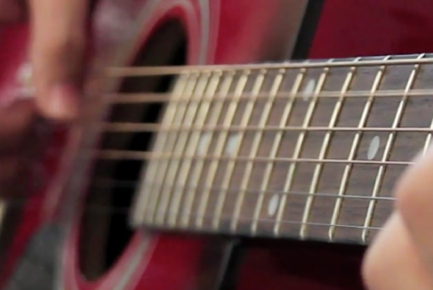 A photograph of a guitar being played.