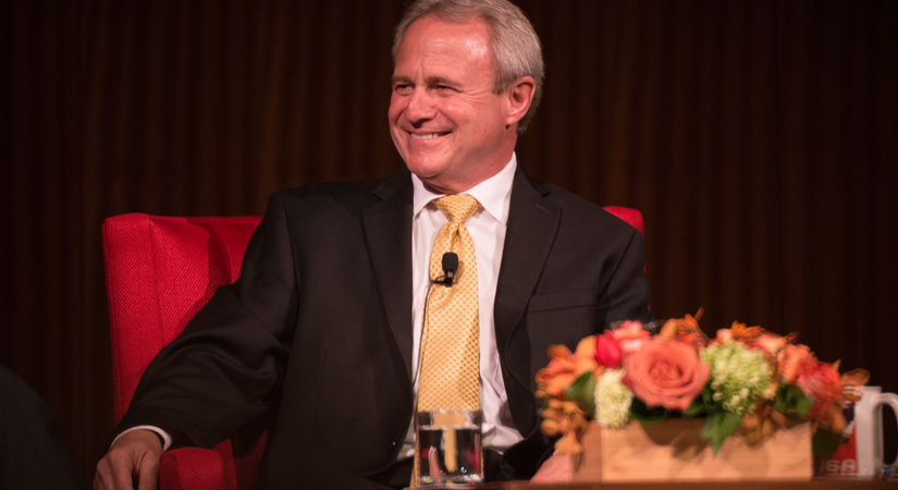 A photo of a smiling man with gray hair, with a microphone attached to his tie.