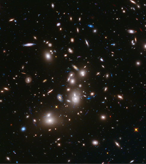 Image of galaxy cluster Abell 2744. Several large, bright elliptical galaxies dominate this cluster of galaxies, which is massive enough to act as a gravitational lens to brighten and magnify the images of nearly 3000 distant background galaxies.