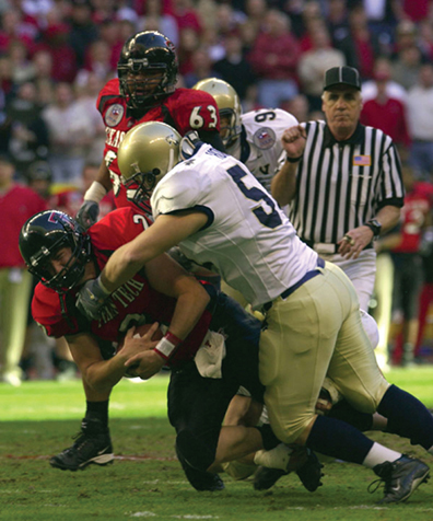 A photo of a football player tackling an opponent.