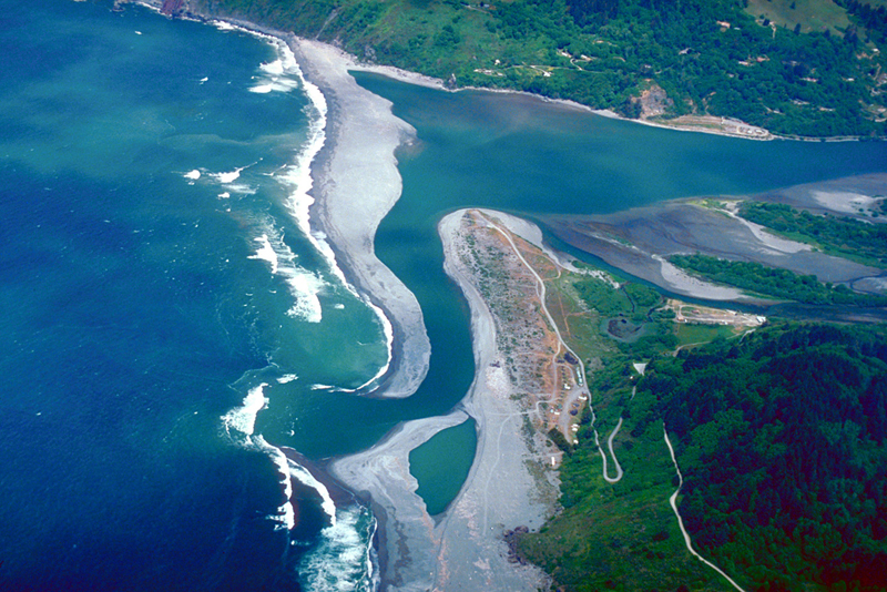 This photo shows an aerial view of the ocean on the left, and a river on the right emptying into the ocean.