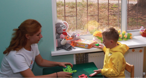 An adult and a child sit and talk at a child's table. Stuffed animals are on a shelf between them.