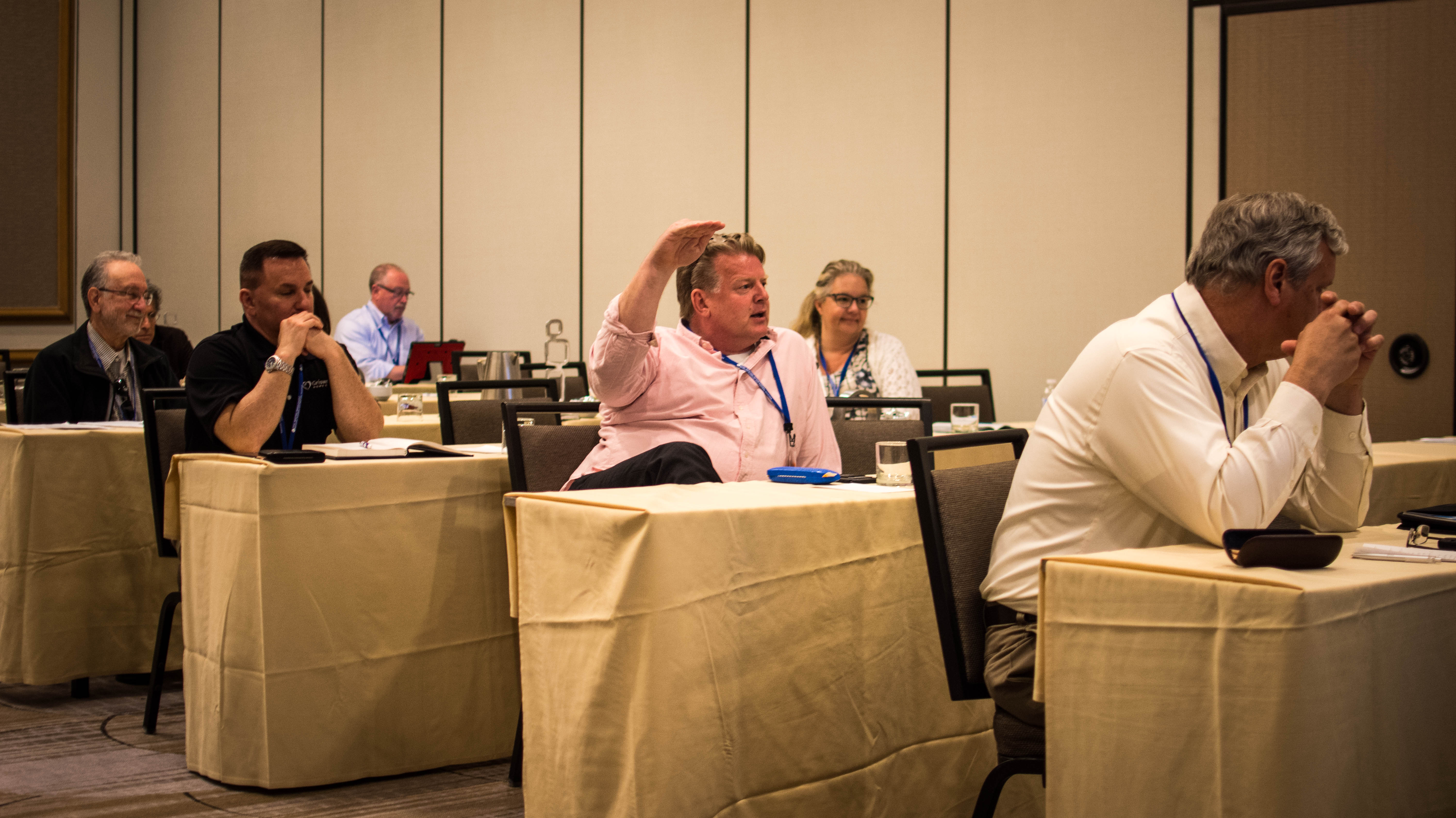 A photo shows Brian Schnell raising his hand vehemently while speaking to other franchisee attorneys during a meeting.