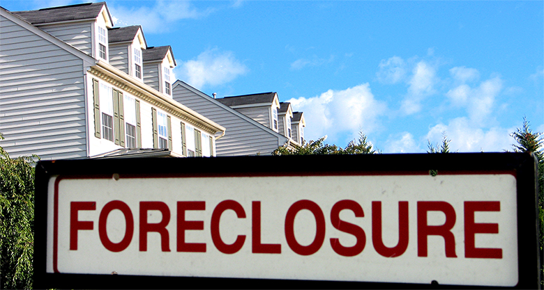 "The image shows a ""Foreclosure"" sign in the foreground and the tops of a couple of houses in the background."
