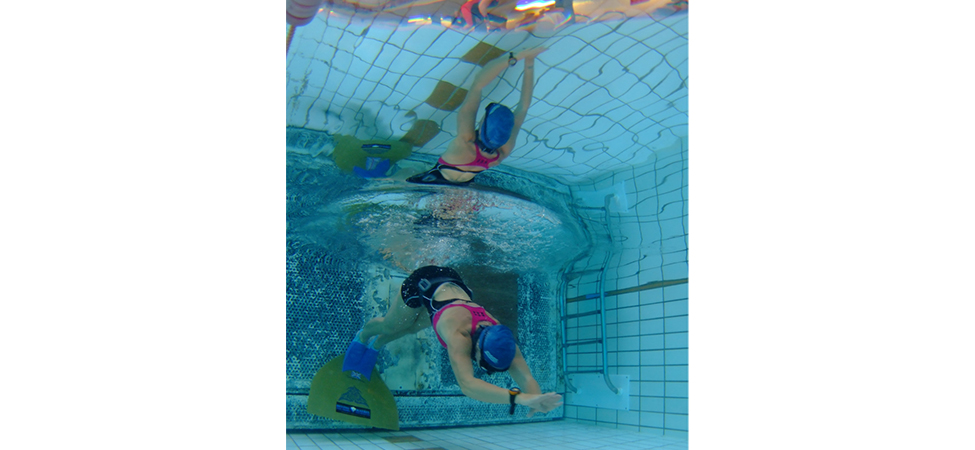 The figure is a photograph taken from underwater. The photo shows an underwater swimmer. Above the swimmer is an upside down image of the swimmer and of the activities on the deck, outside the pool.